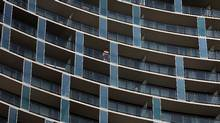 A man looks out from his balcony of a condominium building in the Front Street area in Toronto on March 22, 2012. (Deborah Baic/Deborah Baic/The Globe and Mail)