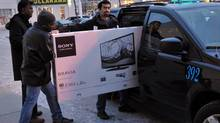 Predawn boxing day bargain hunters load their big screen tv into a cab in front of the Hearland Best Buy store in Mississauga, Dec 26, 2012. (J.P. MOCZULSKI/Toronto)