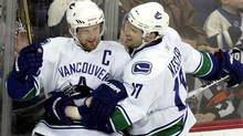 Vancouver Canucks' Henrik Sedin, left, and teammate Ryan Kessler (Paul Vernon/AP)