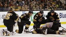 Boston Bruins' Manny Fernandez, left, P.J. Axelsson, Chuck Kobasew and Matt Hunwick kneel over fallen Bruin Patrice Bergeron during the second period of their 4-2 win over the Carolina Hurricanes in a hockey game in Boston on Saturday, Dec. 20, 2008. (Winslow Townson)