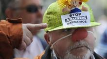A man points at his cap during a protest outside the Liberbank headquarters in Oviedo, northern Spain, May 28, 2012. The words on his cap read, 'Stop bank outrages.' (Eloy Alonso/Reuters/Eloy Alonso/Reuters)