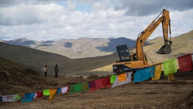 Two workers next to an excavator on the the Lhasa-Nyingchi section of the China National Highway 318 construction, at Milashan pass in China's Tibet Autonomous Region.