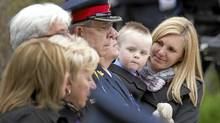 Christine Ryan, wife of slain Toronto police officer Sergeant Ryan Russell, holds their 2-year-old son Nolan while attending the 12th annual Ceremony of Remembrance for Ontario's police officers lost in the line of duty at Queen's Park May 1, 2011. (Darren Calabrese for The Globe and Mail/Darren Calabrese for The Globe and Mail)