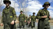 Soldiers from the Royal 22nd regiment, known as the Vandoos, wade through the flooded street along the Richelieu River, Monday, May 9, 2011 in Saint Blaise, qUE. (Ryan Remiorz/RYAN REMIORZ/THE CANADIAN PRESS)