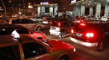 Vehicles wait at a gas station in Shanghai (Pei Xin/AP)