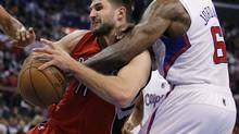 Toronto Raptors' Linas Kleiza, left, of Lithuania, is fouled by Los Angeles Clippers' DeAndre Jordan in the second half of an NBA game in Los Angeles, Sunday, Dec. 9, 2012. (Jae C. Hong/AP)
