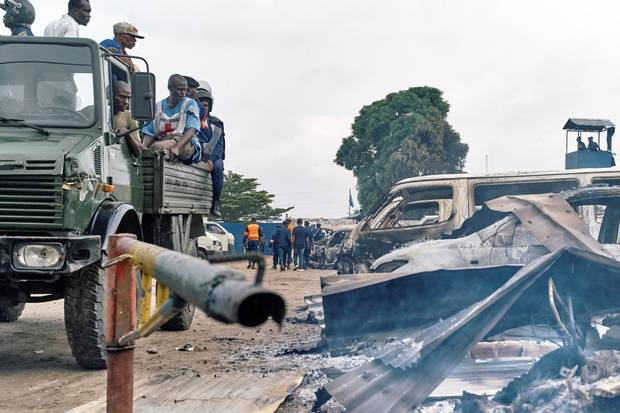 Security personnel sitting on a truck watch burned vehicles at the front gate of the Makala prison after it was attacked by supporters of jailed Christian sect leader Ne Muanda Nsemi in Kinshasa, Democratic Republic of the Congo May 17, 2017.