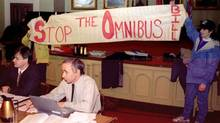 Protesters hold up a sign during a hearing into the Ontario government's controversial Bill 26 omnibus bill in Kingston, Ont., in 1996. (The Canadian Press/The Canadian Press)