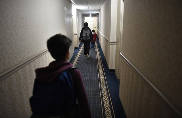 Ahmad Al Rasoul's sons head down the hallway to their apartment after school was over at nearby Thorncliffe Park School.