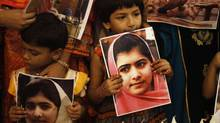 "Children of supporters of the Muttahida Qaumi Movement (MQM) party hold potraits of Malala Yousufzai in Karachi November 10, 2012. UN officials declared ""Malala Day"" one month after 15-year-old Malala Yousufzai and two of her classmates were shot by the Pakistan Taliban. She had been targeted for speaking out against the insurgency. (ATHAR HUSSAIN/REUTERS)"