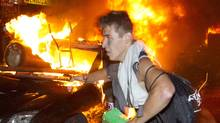 Looters from the Bay run past a burning car set off by rioters in Vancouver, June 15, 2011. (JOHN LEHMANN/The Globe and Mail)
