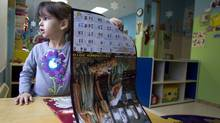 Carina D'Angelo looks through the school's calendar in her classroom at The Friends of Don Bosco Daycare in Riviere des Prairies, Quebec, December 21, 2010. (Christinne Muschi/Christinne Muschi/The Globe and)