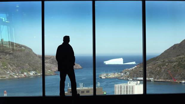 A man looks out at St. John's from The Rooms, a public cultural space.