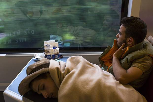 A Syrian refugee gazes out the window at the Austrian countryside while riding a train bound for Munich, Germany in September 2015.