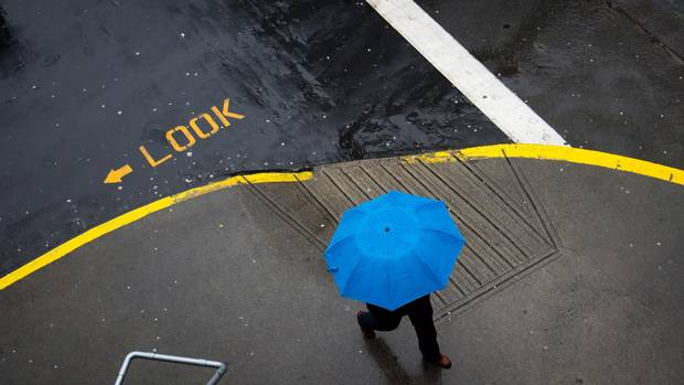 A man carries an umbrella while walking in downtown Vancouver in April 2014.