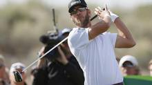 Graham, DeLaet, of Canada, lets go of his golf club after hitting his tee shot at the 15th hole during the final round of the Phoenix Open golf tournament on Sunday, Feb. 2, 2014, in Scottsdale, Ariz. (Ross D. Franklin/The Associated Press)