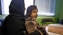 Days after arriving in Canada, an Afghan girl, 7, sits on her mother's lap at the Afghan Women's Organization in Toronto on Feb. 2, 2012. (JENNIFER ROBERTS FOR THE GLOBE AND MAIL/JENNIFER ROBERTS FOR THE GLOBE AND MAIL)