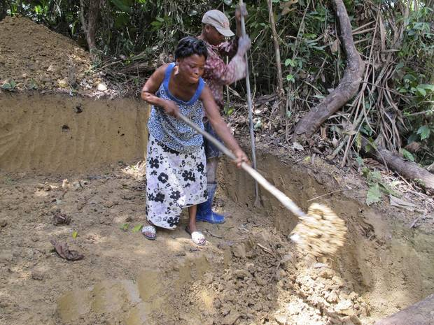 Mami Basikawike, left, and Germain Kambale dig up soil as they search for gold at a small mining site near Metale. She says female miners are subjected to a double standard by being required to dress modestly and avoid wearing ripped clothes.
