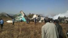 People gather at the wreckage of a Air Bagan Fokker-100 passenger jet that crashed in Heho Dec. 25, 2012. (Reuters)