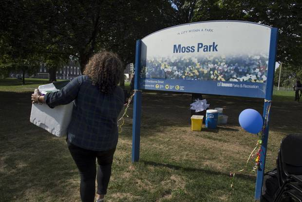 A volunteer carries supplies to Moss Park as the site is set up.