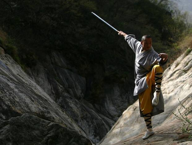 A warrior monk of the Shaolin Temple displays his Kung Fu skills at the Songshan Mountain.