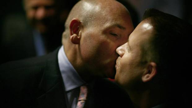 George Smitherman (L)  kisses husband Christopher Peloso after a press conference at Queen's Park where he announced he will run next year for mayor of Toronto on November 9, 2009. (Fernando Morales/The Globe and Mail)