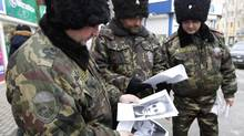 Russian cossacks look at portraits of people suspected of involvement in terrorist acts (VASILY FEDOSENKO/REUTERS)