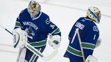 A dejected looking Vancouver Canucks' goalie Roberto Luongo (R) skates past Cory Schneider (L) after Luongo was pulled during the scond period of the game five against the Chicago Blackhawks of an NHL Western Conference quarterfinal Stanley Cup playoff series in Vancouver April 21, 2011. (JOHN LEHMANN/The Globe and Mail)