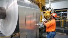A worker inspects a finished rolls of aluminum at the Alcoa Warrick Operations in Newburgh, Ind. (DANIEL R. PATMORE/AP)