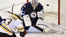 Boston Bruins' Brad Marchand (L) scores the game-winning goal on Winnipeg Jets goaltender Ondrej Pavelec during the third period of their NHL hockey game in Winnipeg February 17, 2013. (FRED GREENSLADE/REUTERS)