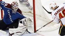 Calgary Flames winger Alex Tanguay (R) gets the puck just off the tip of his stick into a narrow gap under the glove of Colorado Avalanche goalie Peter Budaj to score in their NHL hockey game in Denver April 3, 2011. The Flames won 2-1. REUTERS/Rick Wilking (RICK WILKING)