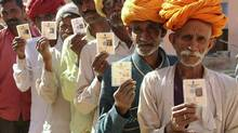 Villagers pose with their identity cards as they stand in line to open a bank account in a village at Ajmer in Rajasthan, Jan. 10, 2013. New Delhi plans to directly transfer cash payments for subsidies into these private bank accounts, a move aimed at tackling graft in India's creaky, corruption-ridden public distribution system. (STRINGER/INDIA/REUTERS)