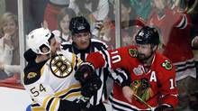 A referee tries to break up a fight as Boston Bruins defenceman Adam McQuaid (54) goes after Chicago Blackhawks centre Patrick Sharp (10) during the second period of Game 1 in their NHL Stanley Cup Final series,Wednesday, June 12, 2013 in Chicago. (Charles Rex Arbogast/AP)