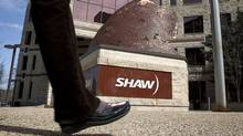 People walk past the headquarters of Shaw Communications in Calgary, Alta., Wednesday, April 13, 2011. (Jeff McIntosh/Jeff McIntosh/THE CANADIAN PRESS)