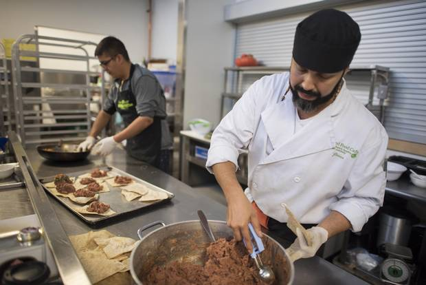 Kenai Meawasige, left, and Jesus Gomez prepare lunch for staff and guests at Food Share, which relocated to Industry Street.