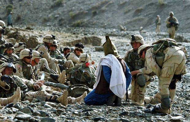 Soldiers of the U.S. 82nd airborne detain an Afghan man during Operation Alamo Sweep in southeastern Afghanistan on Nov. 7, 2002. The U.S. military refers to people detained on missions in Afghanistan for questioning as
