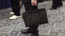 A man holds his briefcase at a job fair in New York last month. The broad and deep decline in public hiring is a significant shift in the United States labour market. (SHANNON STAPLETON/REUTERS)