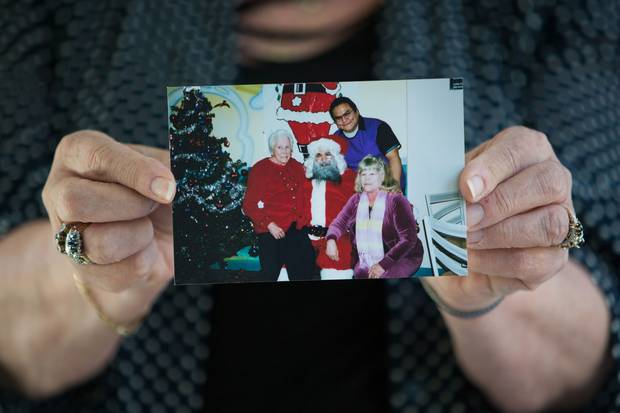 Robyn Batryn holds a Christmas picture of herself, Phillip Tallio and her mother.
