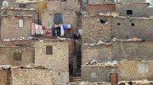 A resident of the shanty area of al-Dweiqa in Cairo squats near his house October 4, 2012. (MOHAMED ABD EL GHANY/REUTERS)