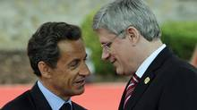 French President Nicolas Sarkozy speaks to Prime Minister Stephen Harper upon arrival at the G8 summit in Deauville, France, on May 26, 2011. (POOL/Reuters)