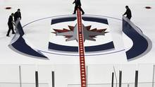 Winnipeg Jets staff lay down the Jet logo at centre ice of MTS Centre in Winnipeg on Tuesday, January 8, 2013. (JOHN WOODS/THE CANADIAN PRESS)