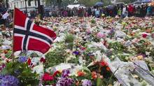 People gather to offer flowers in tribute to the victims of Friday's twin attack in Oslo outside the cathedral of Oslo Sunday. (BERIT ROALD/REUTERS/BERIT ROALD/REUTERS)