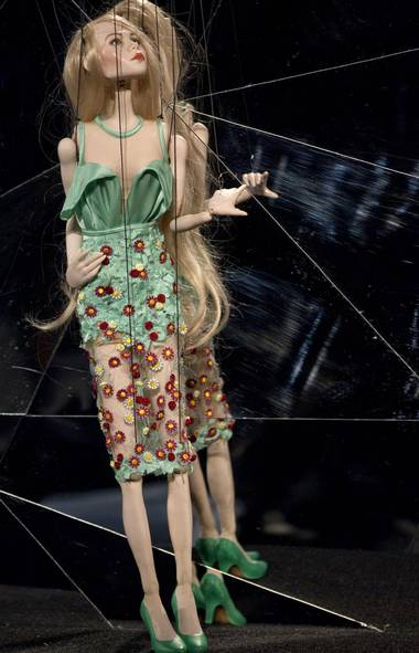 A puppet, about 30 inches high, wears a tiny ensemble by the Fause Haten summer collection. After the puppet show, the real-sized collection was showcased by models. (Andre Penner/AP)