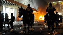 Police on horseback ride through the street past a fire on June 15, 2011, in Vancouver. (Rich Lam/Getty Images/Rich Lam/Getty Images)