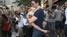 Tom Cruise carries his daughter Suri past a group of photographers as they make their way from a hotel in New York, July 17, 2012. (KEITH BEDFORD/Reuters)