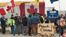 CAW workers picket outside at the Electro-Motive plant in London, Ont., on Feb. 3, 2012, the same day that U.S.-based heavy equipment maker Caterpillar Inc. announced it was closing the plant and moving its production to Indiana. (Mark Spowart/THE CANADIAN PRESS)