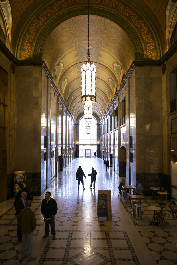 People walk through the main arcade of the Fisher Building.