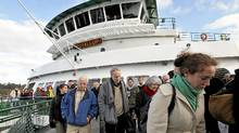 Passengers disembark from the Washington state ferry Puyallup on its arrival on Bainbridge Island, Wash., Wednesday, Dec. 21, 2011. (Elaine Thompson/The Associated Press/Elaine Thompson/The Associated Press)