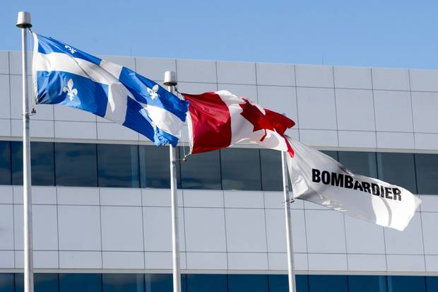 Flags fly outside a Bombardier plant in Mirabel, Que.