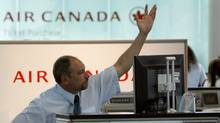 An Air Canada employee gestures for the next passenger at the check-in counter at Pearson International Airport in Toronto (MIKE CASSESE/REUTERS)